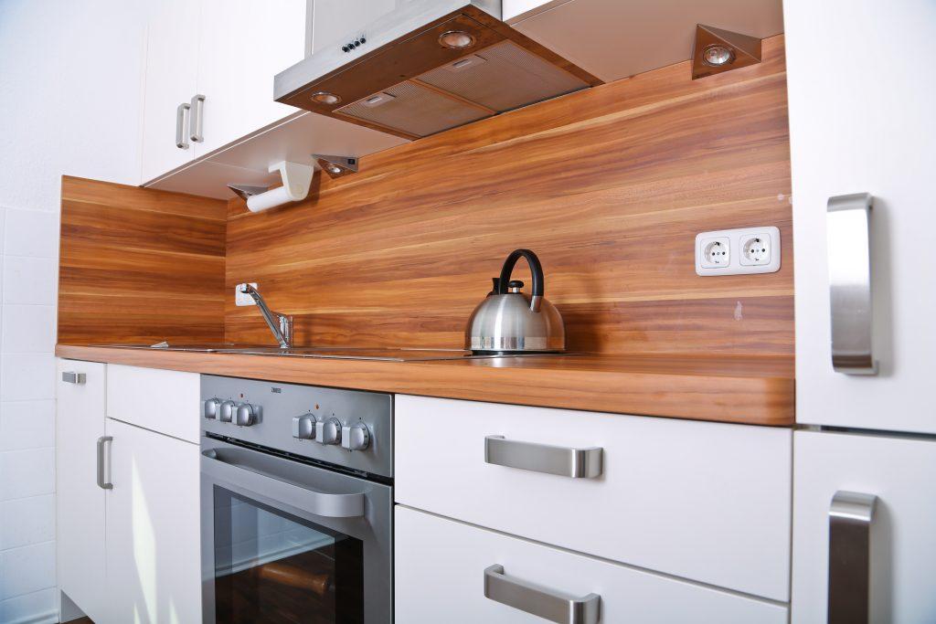 Weiße küche mit dunkler holzarbeitsfläche
